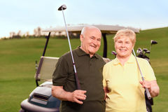Senior man and woman on background of cart. Satisfied with game. Two lovely senior people standing with golf clubs on background of cart on course Stock Photography