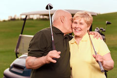 Senior man and woman on background of cart. Showing love. Senior men with golf club giving kiss on cheek to his wife on background of cart on course Stock Photo
