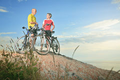 A senior man and a woman bike sunset. Royalty Free Stock Images