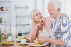 Senior man and woman at breakfast. Smiling senior men and women at breakfast in their house stock images