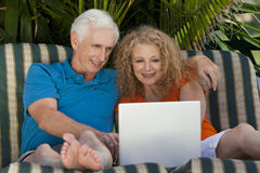 Senior Man and Woman Couple Using Laptop Computer. A senior retired man and woman couple sitting outside on sun loungers using a wireless laptop computer to surf Stock Image