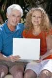 Senior Man & Woman Couple Using Laptop Computer. A senior retired man and woman couple sitting outside using a wireless laptop computer to surf the internet Royalty Free Stock Images