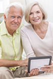 Senior Man & Woman Couple Using Tablet Computer. Happy senior men and women couple sitting together at home on a sofa using a tablet computer royalty free stock photos