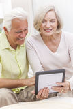 Senior Man & Woman Couple Using Tablet Computer. Happy senior men and women couple sitting together at home on a sofa using a tablet computer stock photo