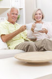 Senior Man & Woman Drinking Tea Coffee at Home. Happy senior men and women couple sitting together at home on a sofa drinking cups of tea or coffee royalty free stock images