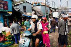 Senior man and woman drive the bike past a market. Senior man and woman drive the bike through the flower market in Calcutta. 0.81% of the Kolkatas workforce Stock Photo