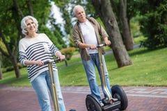Senior man and woman driving modern transport stock photos