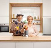 Senior man and woman with a fruit in a blender and a glass of fruit juice stock images