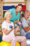 Senior man and woman in gym doing Royalty Free Stock Image