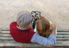 A senior man and woman hand using a touchscreen cell phone Stock Images