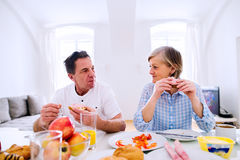 Senior man and woman having breakfast. Sunny morning. Stock Photos