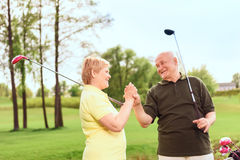 Senior man and woman holding hands together. One team. Smiling senior men and women standing on course holding golf clubs and their hands together Stock Photos
