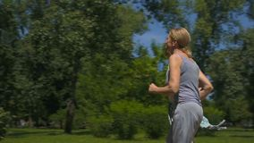 Senior man and woman jogging in park, health care, active people slow-motion