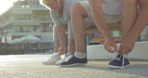 Senior man and woman lacing shoes before training stock video