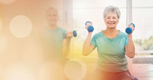 Senior man and woman lifting dumbbells royalty free stock photography