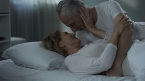 Senior man and woman lying in bed and nuzzling, happily married, tenderness