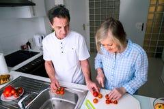 Senior man and woman preparing breakfast. Sunny morning. Royalty Free Stock Photos
