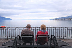 Senior man and woman relaxing at lake Geneva, Switzerland Royalty Free Stock Photos