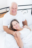 Senior  man and   woman resting on   bed Stock Photography