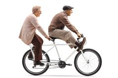 Senior man and woman riding a tandem bicycle with legs up. Full length shot of a senior men and women riding a tandem bicycle with legs up  on white background stock photography