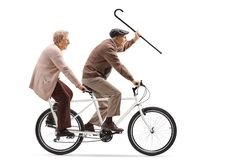 Senior man and woman riding a tandem bicycle and waving with a walking cane stock image