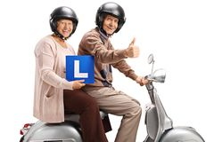 Senior man and woman on a scooter with learner`s plate stock photography