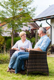 Senior man and woman sitting in front of house. Couple of men and women sitting in front of their home or house in wicker chairs Royalty Free Stock Photos