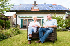 Senior man and woman sitting in front of house Stock Image