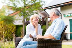 Senior man and woman sitting in front of house Stock Photos