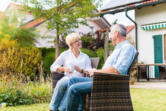 Senior man and woman sitting in front of house Stock Images