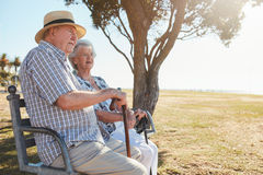 Senior man and woman sitting on a park bench outdoors Royalty Free Stock Image