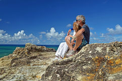 Senior man & woman sitting top of island cliff royalty free stock photo