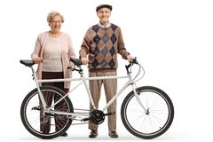 Senior man and woman standing with a tandem bicycle. Full length portrait of a senior men and women standing with a tandem bicycle isolated on white background stock photos