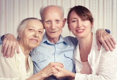 Senior man, woman with their caregiver at home. Royalty Free Stock Images