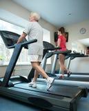 Senior man and woman on a treadmill stock image