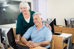 Senior Man And Woman Using Computer In Class. Happy senior men and women using computer in class Royalty Free Stock Photo