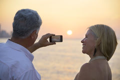 Senior man and woman using mobile phone to take photo Royalty Free Stock Images