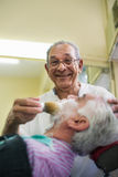 Senior man at work as barber shaving customer Royalty Free Stock Photography