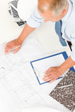 Senior man work on blueprints construction plans. Closeup of senior man working on blueprints and construction plans Royalty Free Stock Image