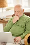 Senior man working on computer at home. Senior man sitting at home, looking at screen of laptop computer, thinking Stock Images