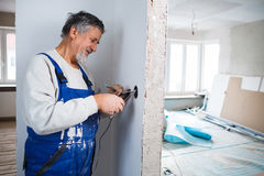 Senior man working on the electrical installations Stock Photos