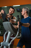 Senior man working in gym with personal trainer. Senior men working out in gym with assistance of personal trainer. Fitness coach showing training plan on stock photo