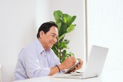 Senior man working with laptop and basic things for work at his. Desk Stock Photo