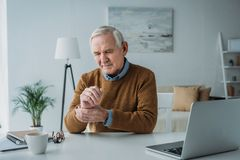 Senior man working on laptop and checking royalty free stock photography