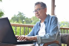 Senior man working on laptop computer at home Royalty Free Stock Image