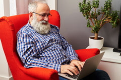 Senior man working with laptop at home Stock Image