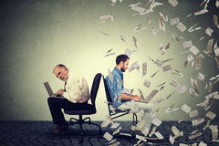 Senior man working on laptop sitting next to young guy using computer under money rain. Royalty Free Stock Photography