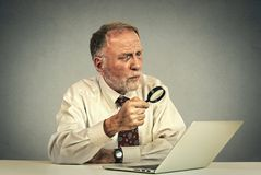 Senior man working looking through magnifying glass at laptop screen Royalty Free Stock Photos