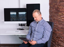 Senior man working in the office Stock Images
