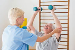 Senior man working out with his therapist Royalty Free Stock Photography